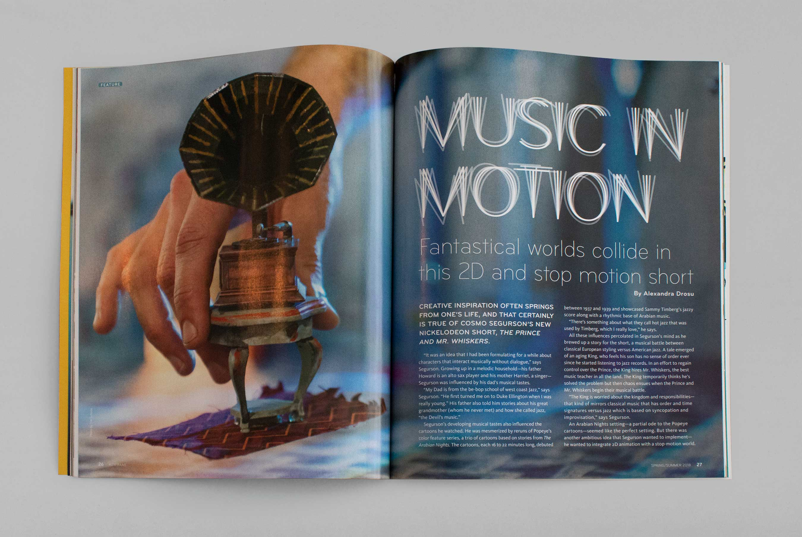 "a magazine feature spread, ""Music in Motion"", with the title on the right page and a hand setting down a small model gramophone on the left page"